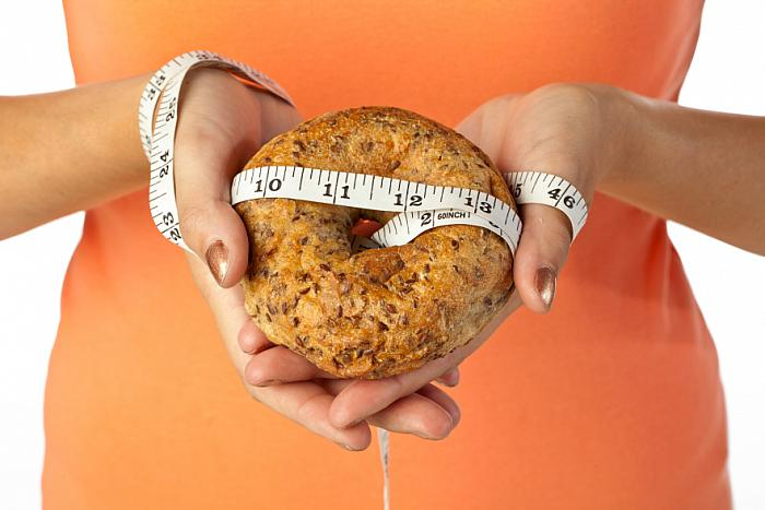 kozzi-766615-human hand holding bread with measuring tape-883x588