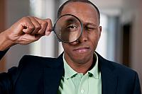 kozzi-3038681-black man looking through a magnifying glass-884x587