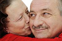 kozzi-2113110-closeup image of elderly woman kissing in a cheek her husband-884x588